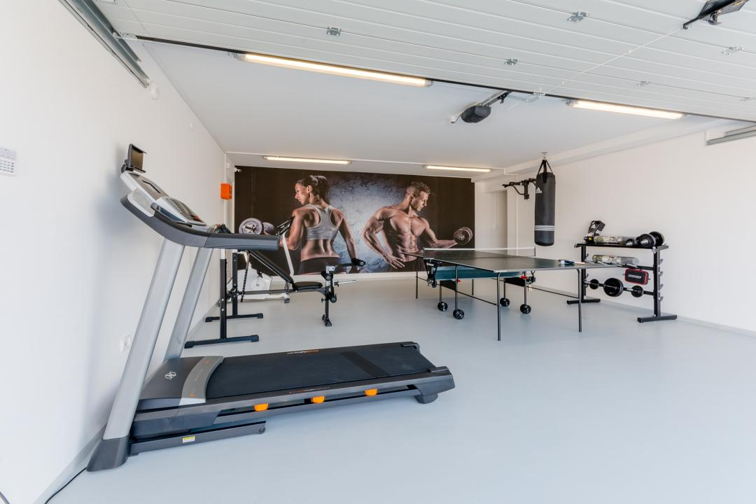 Fitness room in the villa with a big poster on the wall and some equipment around