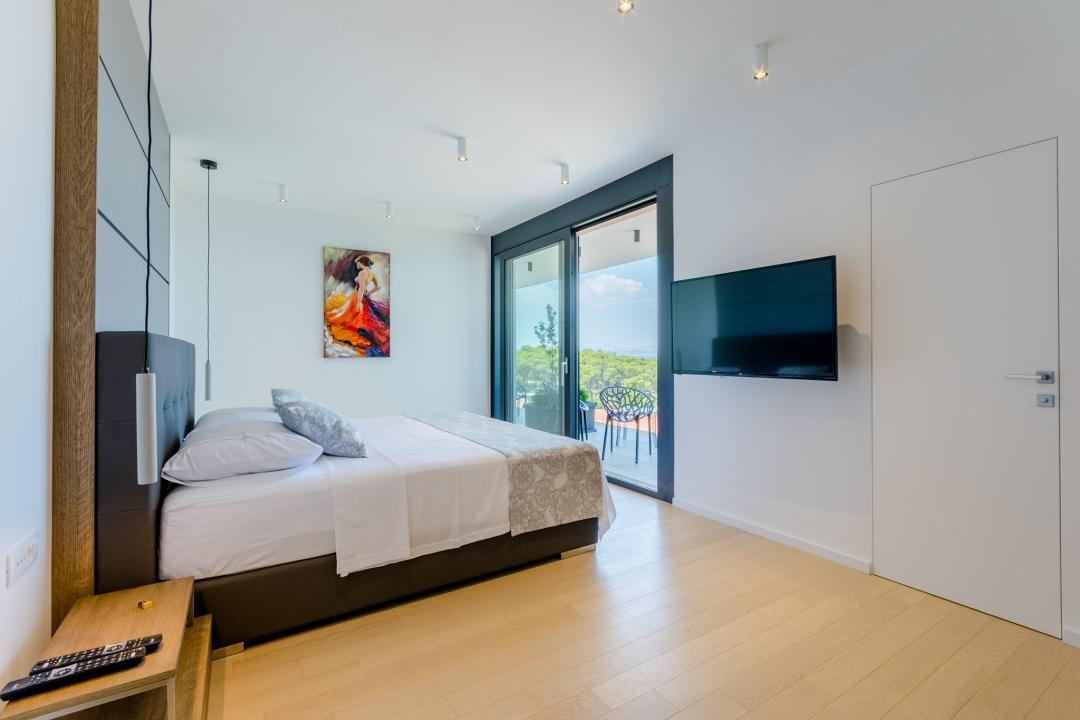 A modern bedroom with a balcony exit