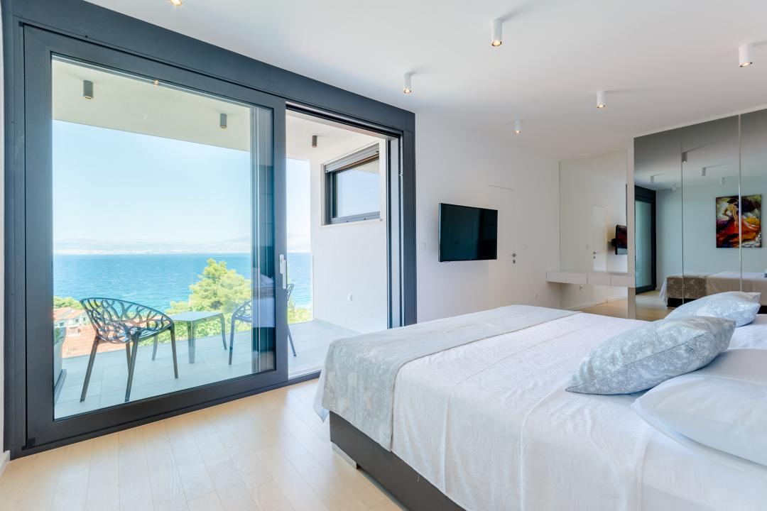 A bedroom with a king-sized bed facing the balcony that has a view on the sea
