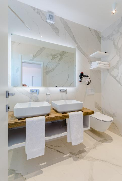 Marble bathroom with a LED lit mirror, 2 sinks and a toilet