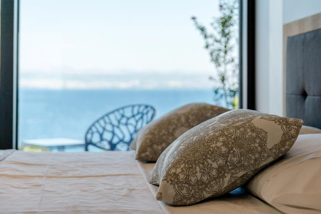 Pillows on a bed with a view on the sea