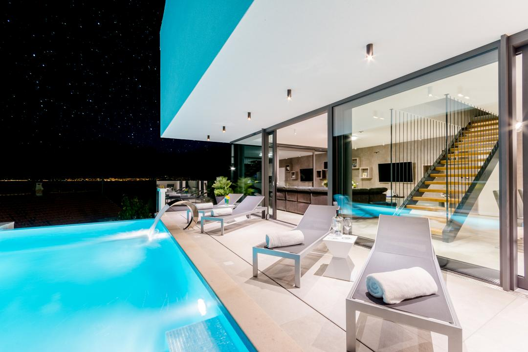 Loungers at the pool in the villa at night